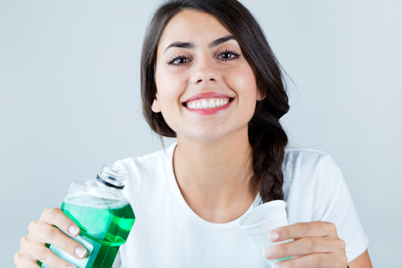 Portrait of beautiful girl using mouthwash. Isolated on white.